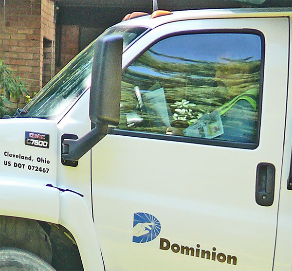dominion gas worker in truck reading newspaper