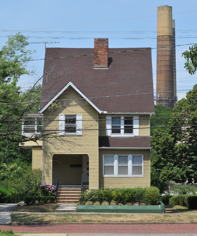 House in Little Italy Ohio, owned by Case, overshadowed by stacks from coal plant