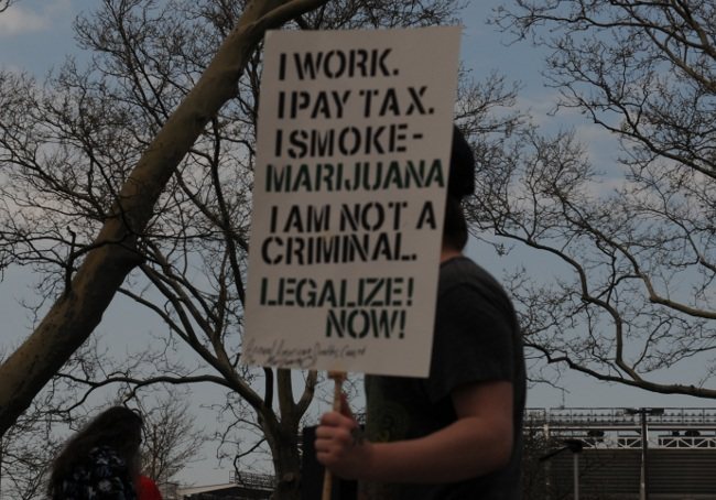 "Medical Marijuana advocate at Cleveland Rally carrying ""I work, I vote, I smoke Marijuana"" sign"
