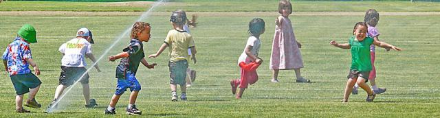 Kids frolic in lawn sprinkler shower - simple pleasure